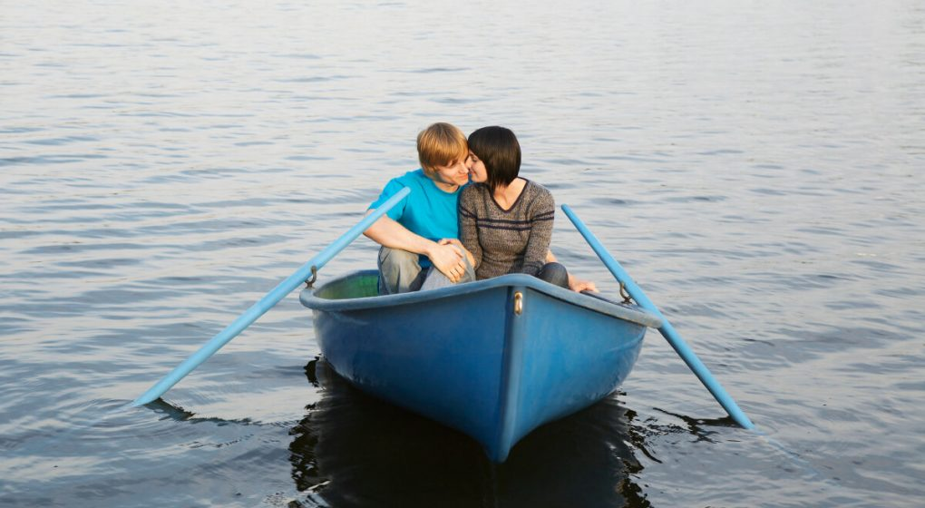 Man and woman on a date in a blue rowing boat