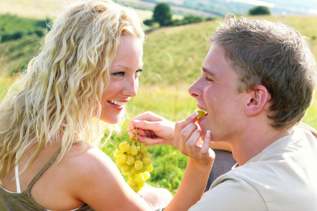 A man and a woman on a date eating grapes