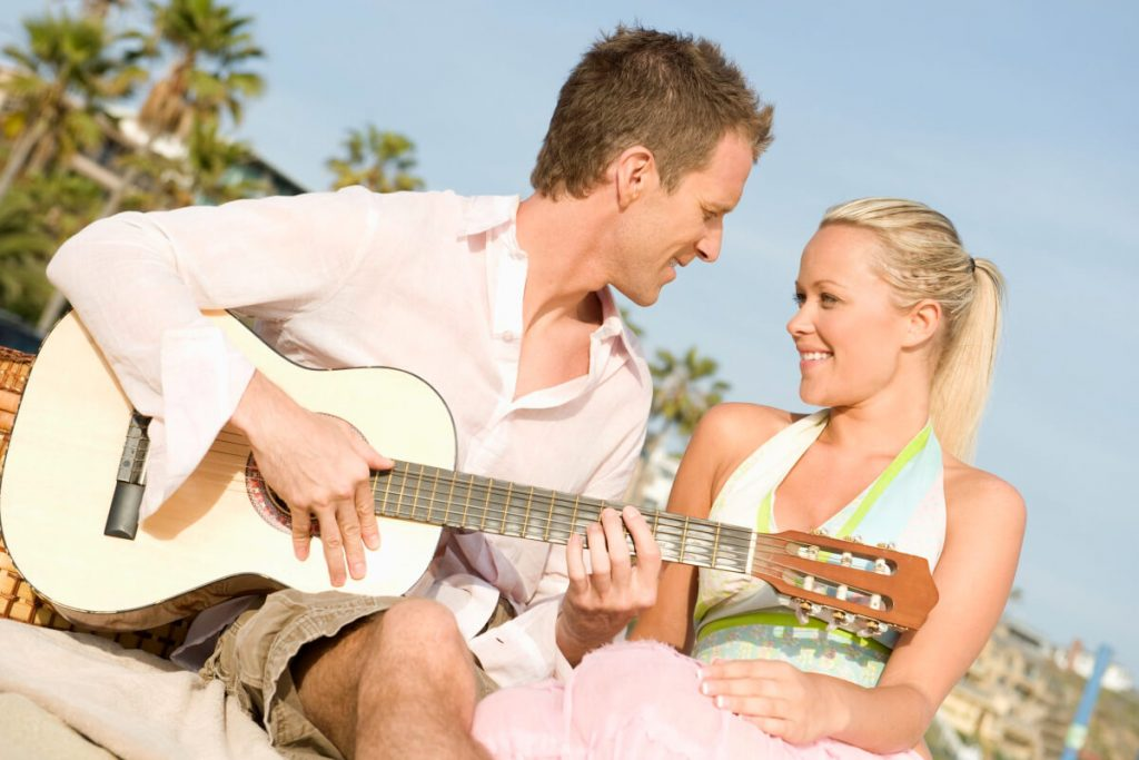 A man playing the guitar to a woman on a date