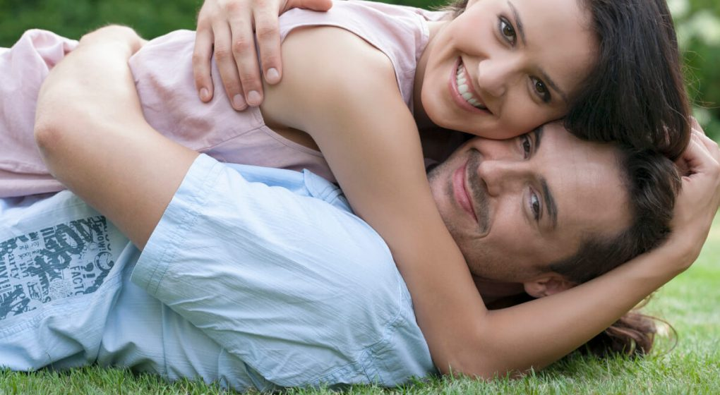 A man dating a woman in the park laying on the ground
