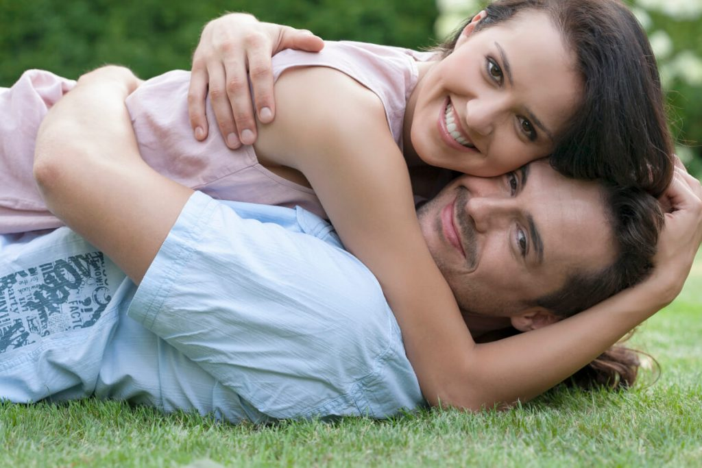 A smiling couple cuddling, while lying on the grass after the woman had stopped the man ignoring her.
