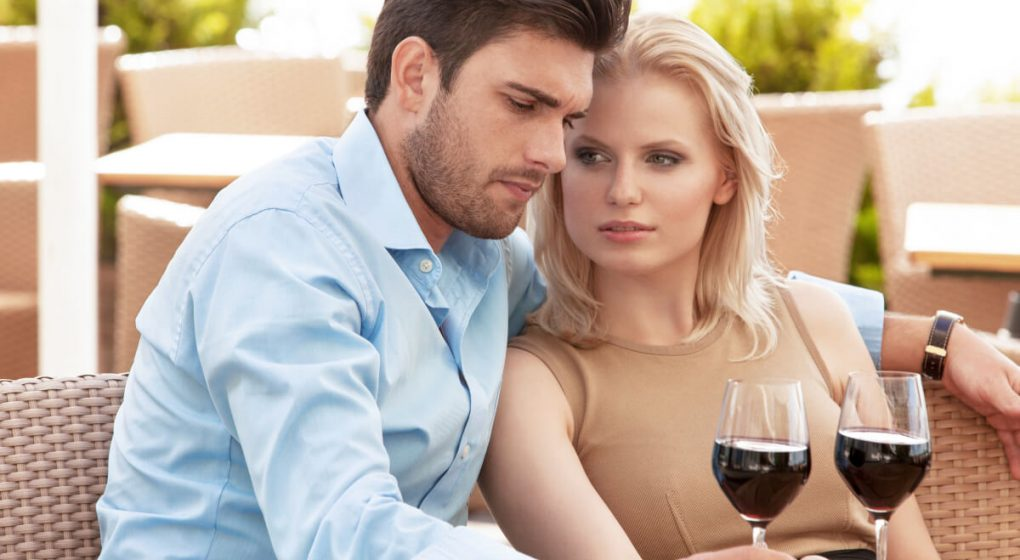 Man ignoring a woman as they sit and drink red wine